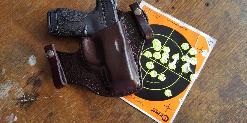 A gun and one of the Best IWB Holsters sitting next to a paper target.