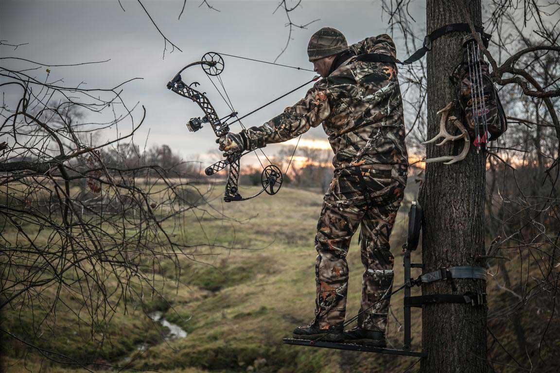 A hunter using a compound bow from a tree stand