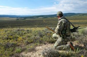 A kneeling camouflaged hunter scans for prey - why hunting is good