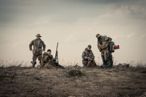 Hunters standing together against sunset sky in rural field during hunting season - why hunting is good