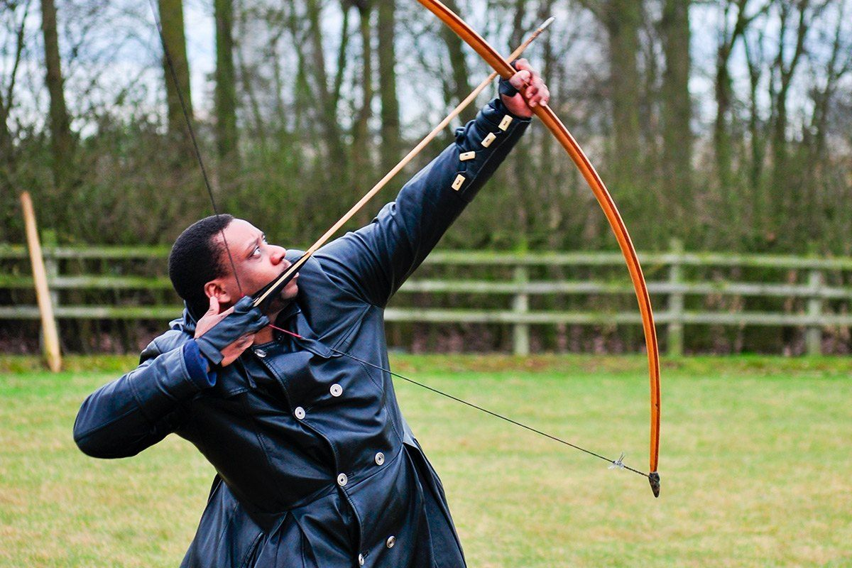 A man using a long bow for target practice