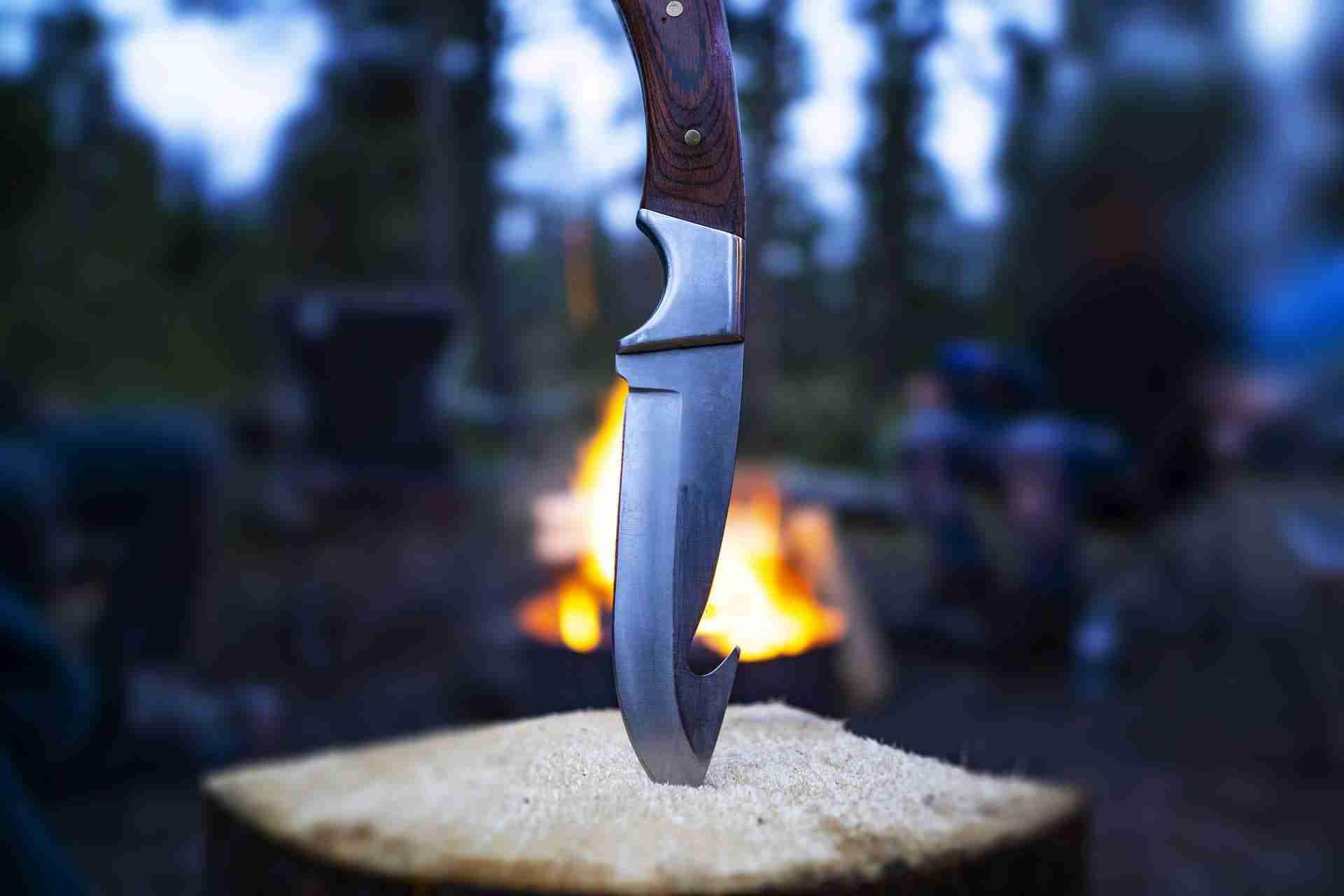 A Cutco hunting knife stuck into a log