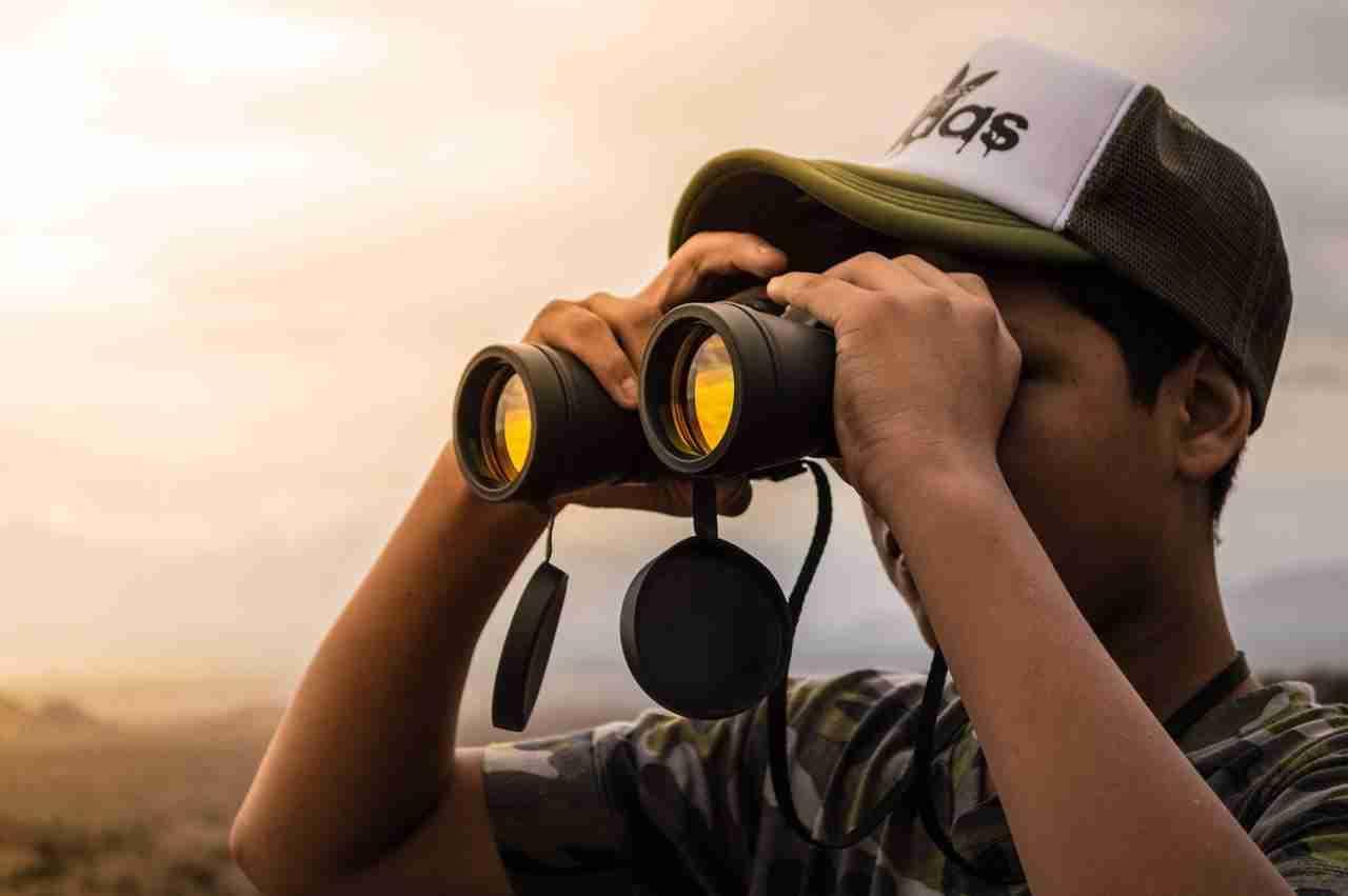 man looking in binoculars